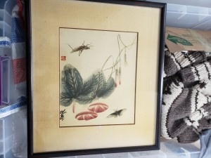 A framed Asian painting of bugs and greenery.