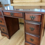 A mahogany desk with drawers.