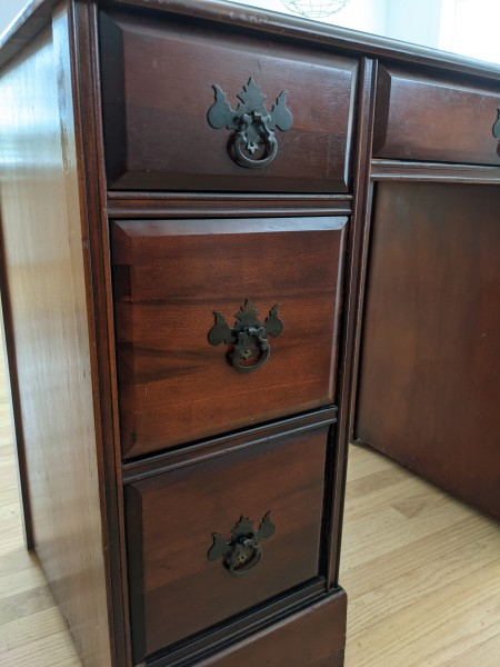 The drawers in a mahogany desk.
