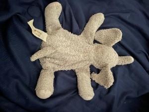 An old stuffed elephant with a torn ear.