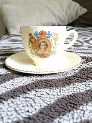 A china cup with the royal seal and a picture of Queen Elizabeth.