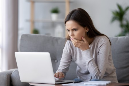 A woman looking at a computer with distress.