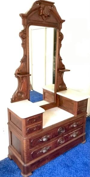 A dresser with a long center mirror.