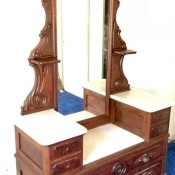 A dresser with a long center mirror.