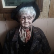 A doll dressed like an old man in a suit with glasses.