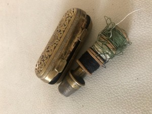 A silver thimble case with a thimble and thread holder.