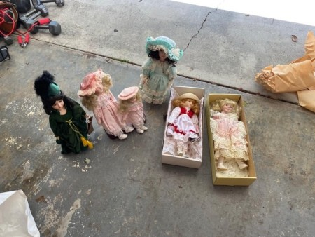 Six porcelain dolls on a driveway, two in boxes.