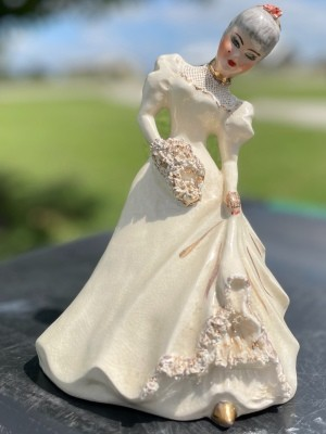 A figurine in an old fashioned dress.