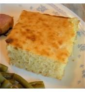 A piece of cornbread on a dinner plate.