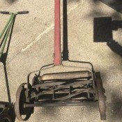 An old reel mower on a driveway.