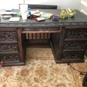 An ornately carved wooden desk.