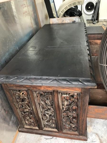 The side of a ornately carved wooden desk.