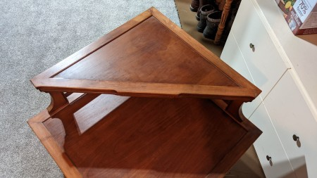 The side of an end table with a triangular shelf.