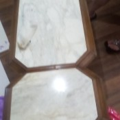 A long wood coffee table with white marble inlays.