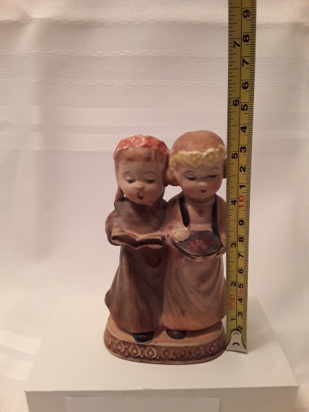 A figurine of two girls, measuring 5 1/2 inches tall.