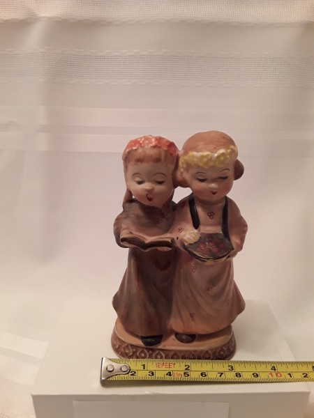 A figurine of two girls, measuring 3 inches wide.
