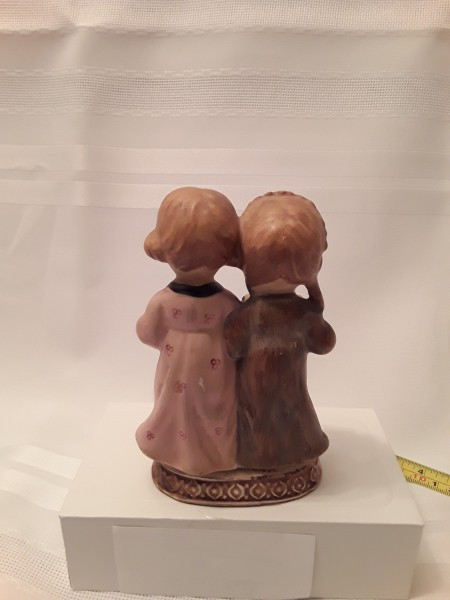 A figurine of two girls from the back.