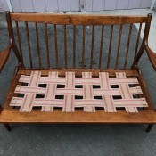 A wooden sofa with a woven seat.
