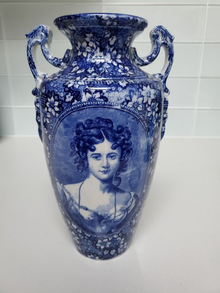 A blue and white vase with an old fashioned ladies face.
