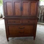 A wooden highboy dresser.