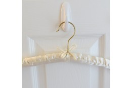 A satin hanger with pearl buttons on the shoulders.