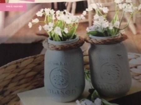 Two decorative mason jars with flowers.