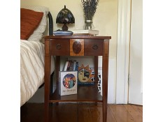 A small wooden end table next to a bed.
