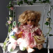 A porcelain doll on a swing.