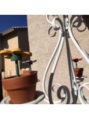 Wooden daisy flowers in terra cotta pots on a chandelier outside.