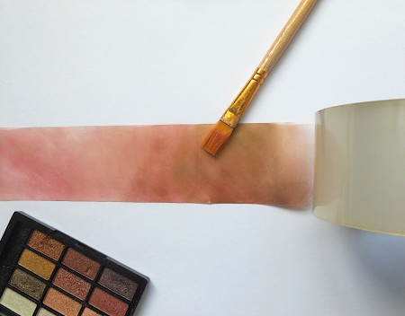 Painting eyeshadow on a piece of tape.