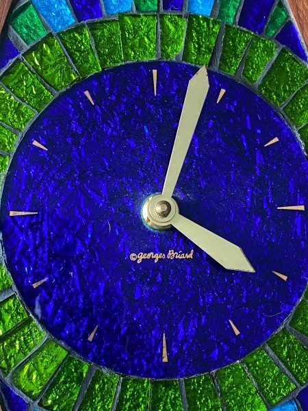 A close up of a stained glass clock face.