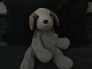 A small brown and white stuffed dog.