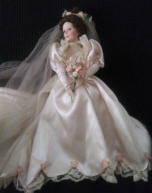 A doll dressed as a bride with a floral bouquet and veil.