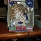 A boxed doll wearing a blue and white outfit.