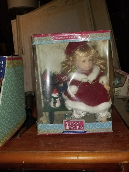 A boxed doll wearing a red dress trimmed in white.