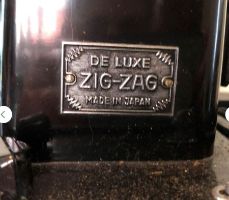 A plaque on the side of a sewing machine.