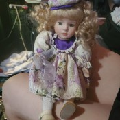 A porcelain doll wearing purple and white.