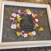 A wedding announcement surrounded by dried flowers.