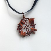 The completed pendant on a ribbon.