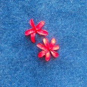 Painted wire flowers attached to denim.