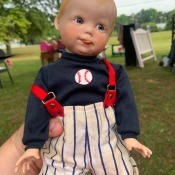 A porcelain doll dressed as a baseball player.