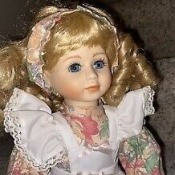 A porcelain doll with blonde hair.