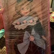 A porcelain doll in a box.