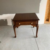 A wooden end table with one drawer.