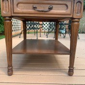 A wooden side table with a drawer.