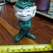 A ceramic elf figurine dressed in green.
