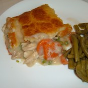 A piece of chicken pot pie on a plate next to cooked green beans.