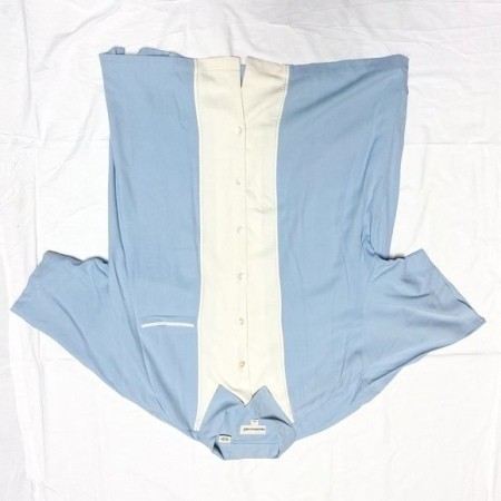 A blue shirt with a white section around the buttons.