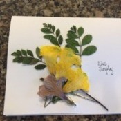 Decorating the card with greenery and flowers.