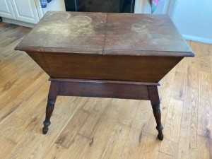 A vintage wooden table with storage underneath.